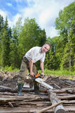 O homem na madeira vê uma árvore uma serra de cadeia Imagem de Stock Royalty Free