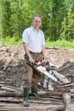 O homem na madeira vê uma árvore uma serra de cadeia Fotografia de Stock Royalty Free