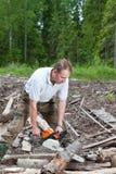 O homem na madeira vê uma árvore uma serra de cadeia Fotos de Stock