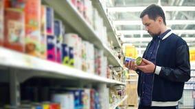 O homem na mercearia escolhe conservas alimentares Ele que está próximo