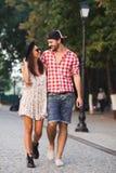 O homem na moda e a mulher modelam caminhadas na rua Imagens de Stock Royalty Free