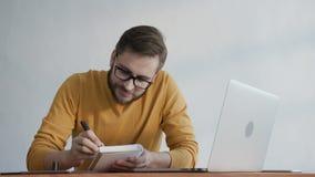 O homem na moda toma notas em um caderno no escritório filme