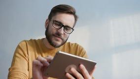 O homem na moda usa o tablet pc para uma comunicação filme