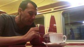 O homem na noite que come a sopa no gato railway do restaurante do trem bebe o café do estilo de vida homem na viagem do conceito video estoque