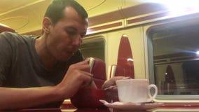 O homem na noite que come a sopa no gato railway do restaurante do trem bebe o café homem do estilo de vida na viagem do conceito vídeos de arquivo