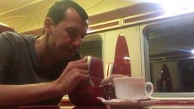 O homem na noite que come a sopa no gato railway do restaurante do trem bebe o estilo de vida do café homem na viagem do conceito video estoque