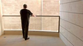 O homem na roupa preta está olhando a parede de seu balcão como um excêntrico video estoque