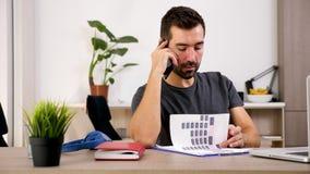 O homem na sala de visitas fala no telefone ao olhar através das cartas financeiras vídeos de arquivo