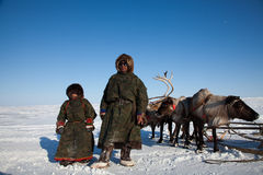 O homem nad de Nenets seu filho perto dos deers Imagem de Stock
