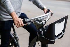 O homem nas calças de brim e na equitação da camiseta bicycle na estrada Imagem de Stock Royalty Free