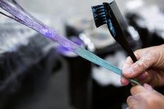 O homem nas luvas é colorfull azul longo de morte do cabelo Salão de beleza, barbeiro imagem de stock royalty free