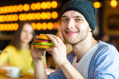 O homem nas mãos guarda um hamburguer Antropófago um hamburguer no café imagem de stock royalty free