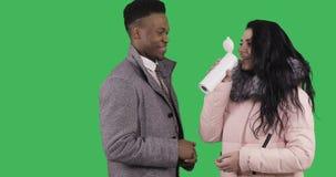 O homem negro afro-americano em um revestimento do inverno trata um café quente moreno atrativo em uma caneca thermo vídeos de arquivo