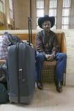 O homem negro com sacos, chapéu de vaqueiro e vaqueiro calça o trem de espera na 30a estação da rua, estação de caminhos-de-ferro Imagem de Stock