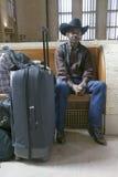 O homem negro com sacos, chapéu de vaqueiro e vaqueiro calça o trem de espera na 30a estação da rua, estação de caminhos-de-ferro Imagem de Stock Royalty Free