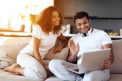 O homem negro e a mulher estão sentando-se no sofá Um homem está sentando-se com um portátil em seu regaço Imagens de Stock