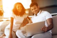 O homem negro e a mulher estão sentando-se no sofá Um homem está sentando-se com um portátil em seu regaço Imagem de Stock Royalty Free