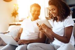 O homem negro e a mulher estão sentando-se no sofá Um homem está trabalhando em um portátil, uma mulher está lendo algo em uma ta Fotos de Stock Royalty Free