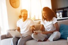 O homem negro e a mulher estão sentando-se no sofá Um homem está trabalhando em um portátil, uma mulher está lendo algo em uma ta Foto de Stock