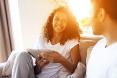 O homem negro e a mulher estão sentando-se no sofá Um homem está trabalhando em um portátil, uma mulher está lendo algo em uma ta Imagens de Stock