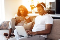 O homem negro e a mulher estão sentando-se no sofá Um homem está trabalhando em um portátil, uma mulher está lendo algo em uma ta Imagem de Stock Royalty Free