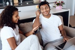 O homem negro e a mulher estão sentando-se no sofá Um homem está trabalhando em um portátil, uma mulher está lendo algo em uma ta Fotografia de Stock Royalty Free