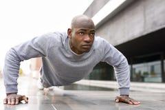 O homem negro que da aptidão exercitar empurra levanta no fundo urbano imagens de stock