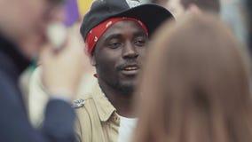 O homem negro vestido como o gângster mostra o gesto de mão na câmera no evento aglomerado filme