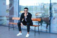 O homem no árabe do terno põe sobre óculos de sol com a tabuleta perto do negócio fotos de stock royalty free