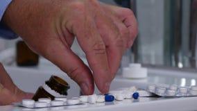 O homem no banheiro escolhe comprimidos para uma cura médica vídeos de arquivo