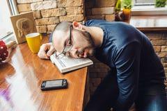 O homem não barbeado nos vidros cansados, caiu adormecido na tabela Foto de Stock Royalty Free