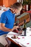O homem no café e escolhe a refeição sob o menu Fotografia de Stock
