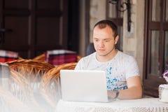 O homem no caffee trabalha em seu portátil Imagens de Stock Royalty Free
