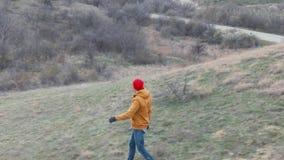 O homem no calor vermelho está caminhando no zangão aéreo do estilo de vida adiantado da saúde dos montes da montanha da mola dis vídeos de arquivo