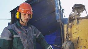 O homem no capacete opera o equipamento de perfuração no campo petrolífero vídeos de arquivo