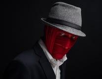 O homem no chapéu, amarrado com a cara vermelha da linha, fundo preto Fotografia de Stock
