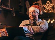 O homem no chapéu e nos vidros de Santa vestidos na camiseta morna guarda o gato e portátil da utilização que comemora o Natal em fotos de stock
