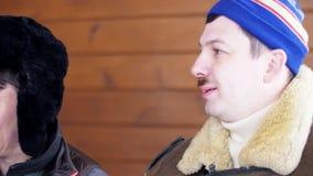 O homem no chap?u e no revestimento azuis senta-se ao lado de seu chap?u vestindo do amigo masculino com aletas da orelha vídeos de arquivo