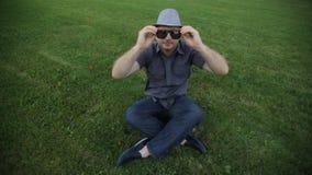 O homem no chapéu veste os óculos de sol que sentam-se na grama vídeos de arquivo