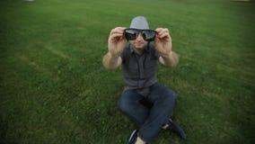 O homem no chapéu veste os óculos de sol que sentam-se na grama filme