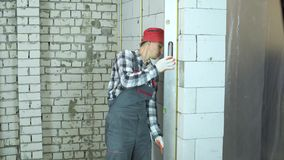O homem no desgaste do trabalho e no tampão vermelho usa a régua da construção para verificar a qualidade da parede filme