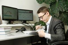 O homem no escritório para monitores do computador estuda registros em um caderno Imagem de Stock