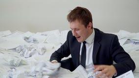O homem no escritório que afoga-se no papel vídeos de arquivo