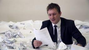 O homem no escritório que afoga-se no papel video estoque