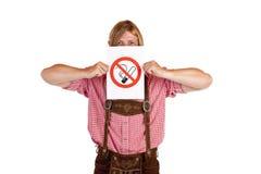 O homem no lederhose prende o sinal da nenhum-fumar-régua Foto de Stock
