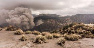 O homem no monte está olhando na erupção do vulcão de Bromo Imagem de Stock Royalty Free