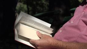 O homem no parque senta-se em um banco relaxou e leu um livro da literatura fotos de stock royalty free