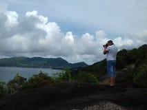 O homem no penhasco que toma imagens do seascape foto de stock