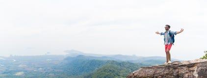 O homem no pico de montanha que levanta as mãos com trouxas aprecia o conceito da liberdade da paisagem, Guy Tourist novo foto de stock royalty free