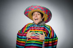 O homem no poncho mexicano vívido contra o cinza Fotos de Stock Royalty Free